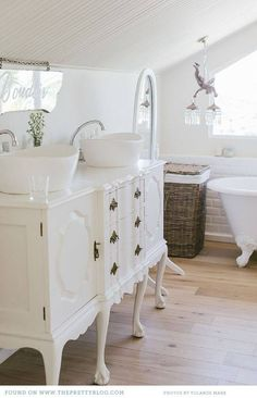 white bathroom and refinished wood flooring
