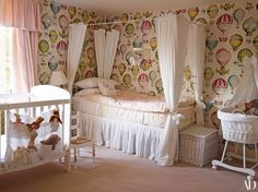 In Nancy's room, Manuel Canovas's L'envol covers the walls, and a Susanna Davis linen dresses the window. Crib by the nursery window, London; antique cast-iron bed with Swiss-Dot voile hangings | archdigest.com