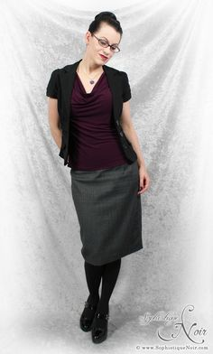 Plum drop neck blouse with a-line charcoal grey skirt, black tights, and black short sleeved blazer