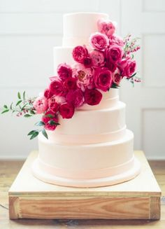Elegant white wedding cake wrapped with pretty pink flowers; Featured Photographer: Loft Photographie