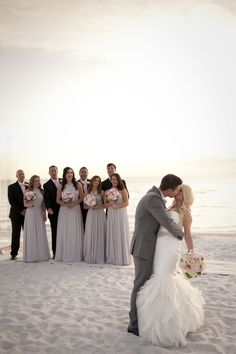 Beach wedding photo with the bridal party looking on