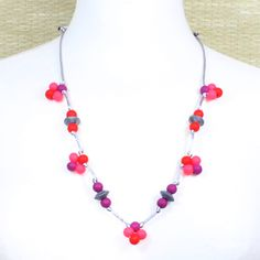 A beautiful combination of pink, red and magenta silicone teething necklace which combines 10mm and 16mm silver beads creating a pretty dainty, ditsy necklace using food grade silicone in pretty flower shapes.