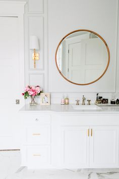 Clean, classic and sophisticated bathroom with marble floors and coutertops, white cabinets, brass mirror and gold sconces.