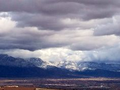 Snow & clouds cover Sandias.