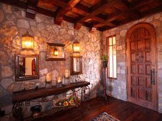 This Old World rustic Spanish entryway designed by architectural designer Matt Dougan features distressed beam work and granite fieldstone, a common element in the mountainous areas of Spain and Mexico. Wood components and tile flooring complete the Old World Spanish look.