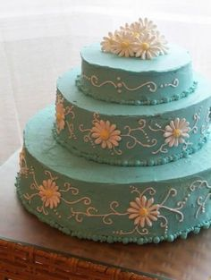 Cake Decorating Inspiration - This is a pretty blue.  The white swirls and daisies stand out nicely.  The swirls are simple and don't overwhelm the cake.  Daisies haven't been my strongest flower.  A little practice would be necessary.