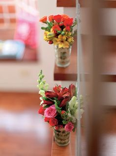 Para deixar a escada em clima de festa, a anfitriã preparou arranjos de flores em porta-velas de vidro