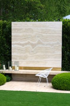 heavenly wall of nocino Travertine marble with band of brass above the floating bench designed by Tommaso del Buono and Paul Gazerwitz for the Telegraph Garden at the RHS Chelsea Flower Show 2014