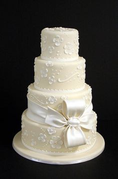 This cream tiered cake's subtle white dots and flowers are topped off with a white fondant bow.