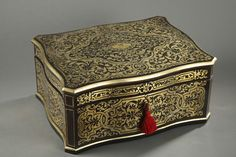A rectangular casket in gilt wood with its laurel crown shaped key, richly decorated with flowery rinceaux, foliage and interlace. The drop-leaf lid is decorated atop with a medallion...