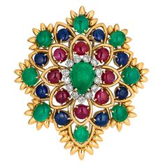 This David Webb multi-colored, gem-set, signed brooch is inspired by nature. A flower in full bloom, this piece features a center cabochon emerald surrounded by diamonds & petals bursting with Burmese color rubies, sapphires & Colombian color emeralds.Circa 1960-1970