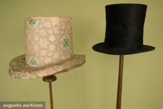 """Gentleman's high hat with box, French, 1830-1860; Black fur felt, narrow black silk ribbon, leather sweat band, paper and silk crown linings, cylindrical tall crown, narrow 2"""" brim, label on crown lining, """"PARAL/RUE GAMMONT/PARIS"""", box shaped to fit hat, covered in beige wallpaper with interlacing star pattern grid with green rosette centers (i love the box!)"""