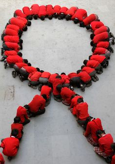 Indian school children form a red ribbon, the universal symbol of awareness and support for those living with HIV, in Ahmadabad, India, Dec. World AIDS Day is marked across the world on Dec.