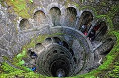 Quinta da Regaleira-Sintra ~ Portugal    An underground tunnel with a spiral staircase, supported by carved columns, down to the bottom of the well through nine landings. The nine hole round landings, separated by fifteen steps, evoke references to Dante's Divine Comedy, and may represent the nine circles of hell, paradise, or purgatory.