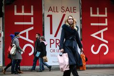 Pedestrians walk past Boxing Day sale signs on display at a BHS Ltd. store on Oxford Street in London, U.K. on Saturday, Dec. 26, 2015. U.K. retail sales volumes increased 1.7 percent from October,...