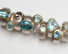 Selection of rings in sterling silver, 18 carat yellow gold, aquamarine.