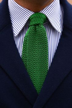 Navy jacket, white shirt with blue stripes, green knit tie