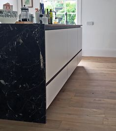 Kitchen Island. Detailed with Noir St Laurent marble and walnut, opening to reveal a walnut and grey laminate interior.