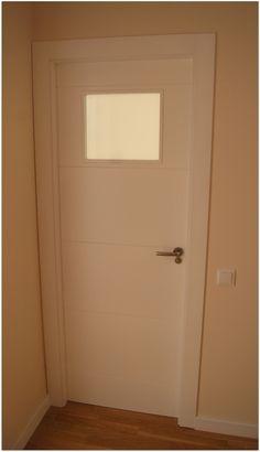 Puerta de dormitorio lacada blanca con cristal al ácido que da luz a un pasillo oscuro.