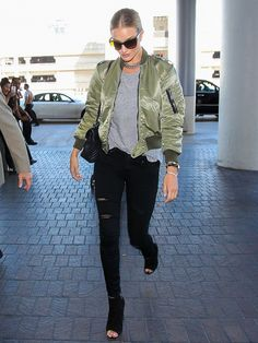 Rosie Huntington-Whiteley wears a gray t-shirt, Saint Laurent bomber jacket, black skinny jeans, peep-toe booties, a shoulder bag, and a silver chain necklace