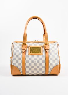 """The """"Berkeley"""" handbag is constructed of Louis Vuitton's iconic """"Damier"""" coated canvas in """"Azur"""" blue and cream. Smooth tan leather trimming and rolled top handles. Glossy gold toned hardware througho"""
