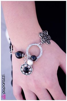 In the Mix Item #: P9RE-BKSV-011XX A black flower with intricate silver detail takes center stage while varying circular silhouettes combine with black beads. Features an adjustable clasp closure.  Sold as an individual bracelet.
