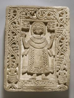Rectangular limestone stela: figure of a haloed figure of Apa Pachom with hands raised; Coptic text beneath the feet with name `Pachom'; border of vine plants with grapes issuing from two amphorae in the lower corners.