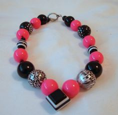 Check out this fun black and hot pink beaded necklace for your little girl or toddler. It features both black and white striped beads as well as animal print beads. It features a toggle clasp for easy on and off and measures approximately 16 inches. (You can specify the length you would like!)
