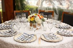 White ruffled round tablecloths, rustic chargers, seagrass floral box
