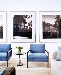 fotos grandes blanco y negro en la pared y los cojines del sofa de rayas azul y blanco