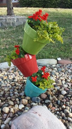 """Colorful Tilted Planter - I found this idea on Pinterest with 5 terra cotta pots. I couldn't find a pole tall enough that would fit thru the hole in the bottom of the pot. I ended up using a 4' piece of rebar and 8"""" painted pots. I love how it spruced up my mailbox!"""