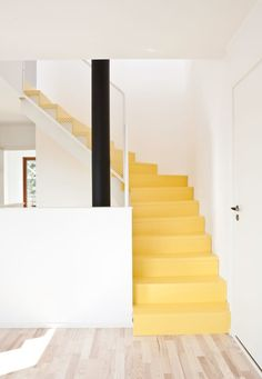 Beautiful old stairs painted in yellow for it to be more prominent - fun and untraditional entryway.
