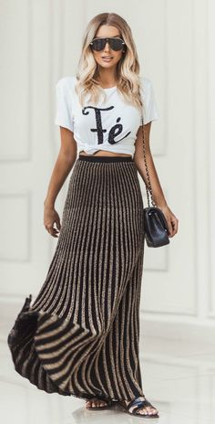 Musa do estilo: Bianca Petry. T-shirt branca estampada com nozinho na cintura, saia plissada preta e dourada, slide