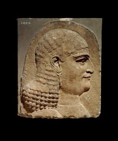 Wall Relief, 710BC-705BC, Neo-Assyrian Stone wall-panel depicting a eunuch in relief: this head, which is over lifesize, belonged to a figure of a eunuch, one of the attendants of the Assyrian king. He wears an earring of a classic Assyrian type, and his curled hair-style is intermediate between that of previous reigns and the shorter squared cut which became fashionable in the seventh century. A pattern of rosettes is embroidered on the neck of his robe.