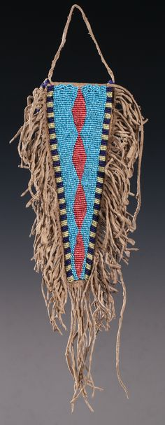 """Nicely shaped Plains tab bag, with vibrantly beaded front panel in colors of cobalt, pale blue, yellow and white-heart red. The beaded edge continues down the flap in the back. Full fringe attached to edges, with longer fringe attached to the tip. The triangular flap is 8"""" long (excluding fringe), it hangs over a 2.75"""" x 2"""" pouch."""