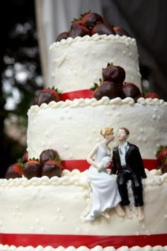Large for tiered wedding cake, with a funny cake topper and chocolate dipped strawberries, for a red and white theme wedding.