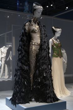 LEFT: Alexander McQueen catsuit and cape with gold and bronze bugle beads, sequins on silk net, and black feathers   RIGHT: Alexander McQueen beige silk tulle dress with green feathers and silver sequins {From the Collection of Daphne Guinness; The Museum at FIT}