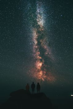 Three people staring at a vibrant starry night sky.