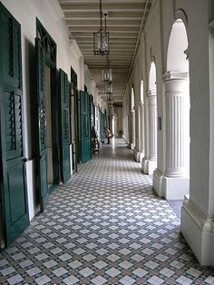 Teal French doors, lanterns, and tiled floors at Singapore Art Museum