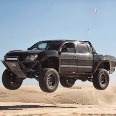 Toyota Tacoma jumping at the dunes