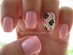 A pretty and detailed plaid nails art design. The design uses a combination of baby pink, white, black and thin strips of gold to complete the overlapping stripes.