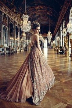 A girl in a beautiful peach gown in an old fashioned hall. Check out my site http://www.designyourownperfume.co.uk to design your own beautiful and unique perfume to compliment your quirky steampunk style:)