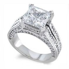 Princess Diamond Accent Engagement Ring - This very luxurious 14k White Gold split-shank Princess Diamond Accent Engagement Ring is Pave set with over 100 lovely White Round Brilliant accent side stones & is perfectly complimented by a beautiful Princess Cut center stone. These white diamonds are well cut & are high in color of H-I & clarity of SI2 (enhanced) gem stones that were very carefully set. The ring's total metal weight is 8 grams & the diamonds are 100% natural…