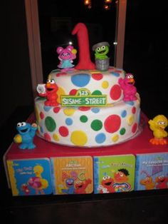 Extraordinary Sesame Street Theme Cake: This cake is fondant covered with different colored fondant circles attached all around it. The characters are all store bought. The cake base is a custom