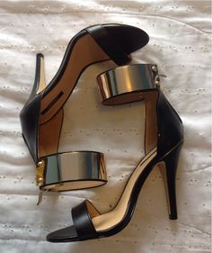Mmmmm I want them! Black high heel sandals with large riveted gold metal on leather ankle straps. Sure to get a rise ;)
