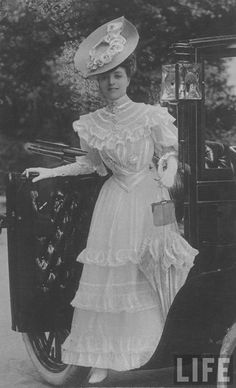 """Vesta Tilly emerging from carriage at Ascot, 1904.""  Fashion trends for women of Edwardian era were characterized by the hourglass silhouette, where the waist was contracted with the use of a corset. The hips and bust were made to look fuller. The trend of that period was ""S-curve"". Blouses and dresses were puffed, high-collar were prevalent, and the waist was narrowed further with a belt."