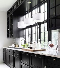 Chic kitchen with black cabinets paired with marble countertops and marble backsplash. Kitchen features polished nickel triple drum pendant over kitchen sink with polished nickel gooseneck faucet and glossy black window moldings.