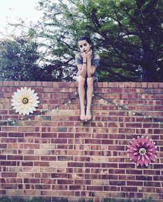 Annie Leblanc sitting on her grandmas brick wall
