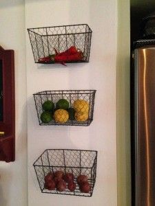 Use metal mesh magazine racks to store produce. The openings let the produce breath, and the baskets look great hanging on the wall filled with colorful fruits and vegetables -- 9 Tips for Kitchen Organization: AHRN.