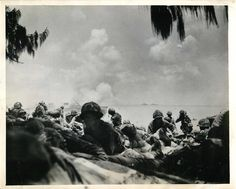 1944- First wave of U.S. Marines to hit the shore on Saipan keep low as they move up the beach under heavy Japanese machine gun fire.